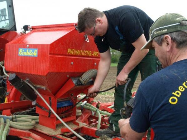 Familie Dreher beim Durchpusten des Schlauchsystems der Saatmaschine